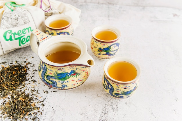 Antique traditional teapot with teacups and dried herbal tea on concrete background Free Photo