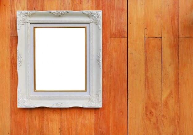 Antique white photo frame with empty space for your picture or text placed on wood plank wall background. Premium Photo