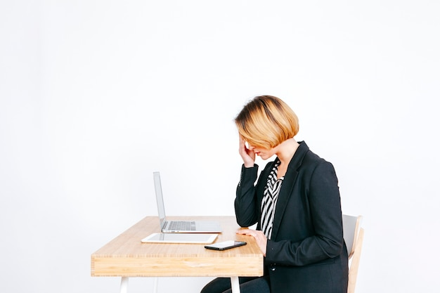 Anxious businesswoman at working place Free Photo