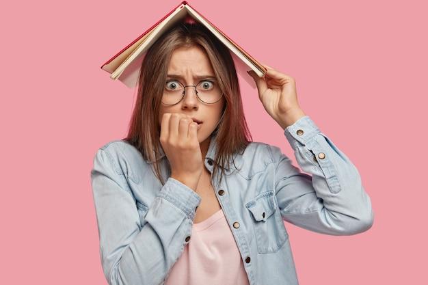 불안한 긴장된 백인 여성은 손톱을 물고, 책을 머리 위에 들고, 시험을 통과하기 전에 걱정하고, 분홍색 배경에 대해 포즈를 취합니다. 학생이 초조해 보인다. 사람과 교육 개념 무료 사진