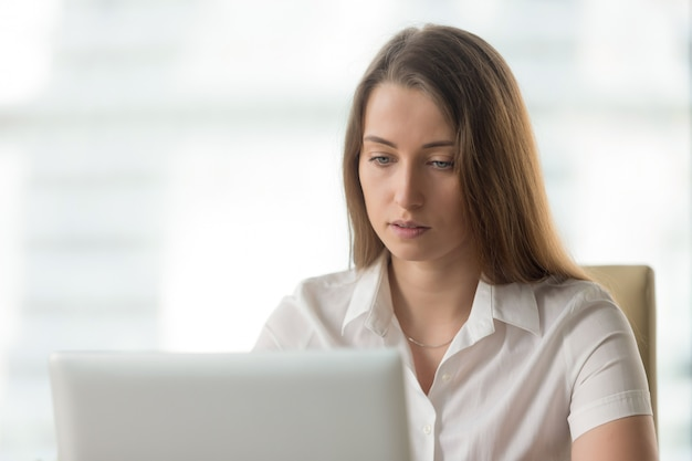Anxious serious businesswoman working on laptop computer, looking at screen Free Photo