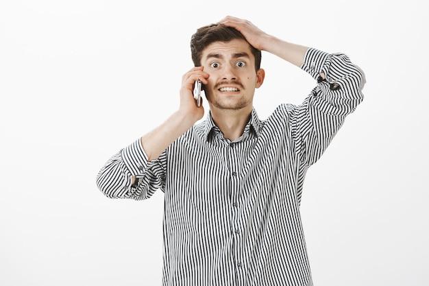 ひげと口ひげを持つ心配しておかしいヨーロッパの男、罪悪感のある緊張した顔をして、スマートフォンで話している間頭に手をつないで、遅れて言い訳をしている 無料写真