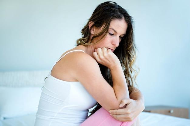 Взволнованная женщина с головой в руках сидит на кровати Premium Фотографии