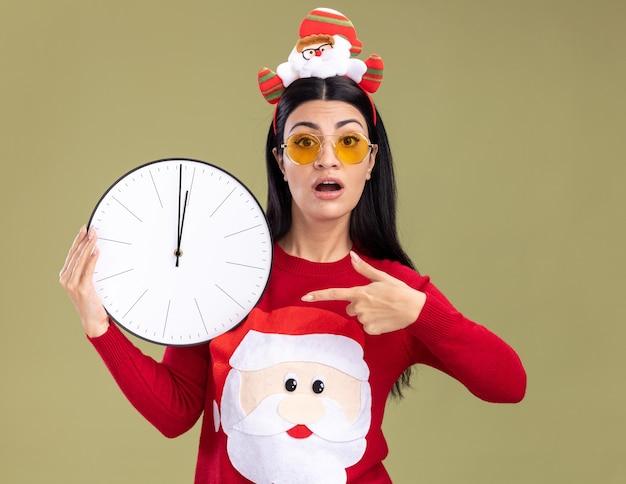 Ansiosa giovane ragazza caucasica che indossa la fascia di babbo natale e maglione con gli occhiali che tengono e che indica l'orologio isolato sulla parete verde oliva Foto Gratuite