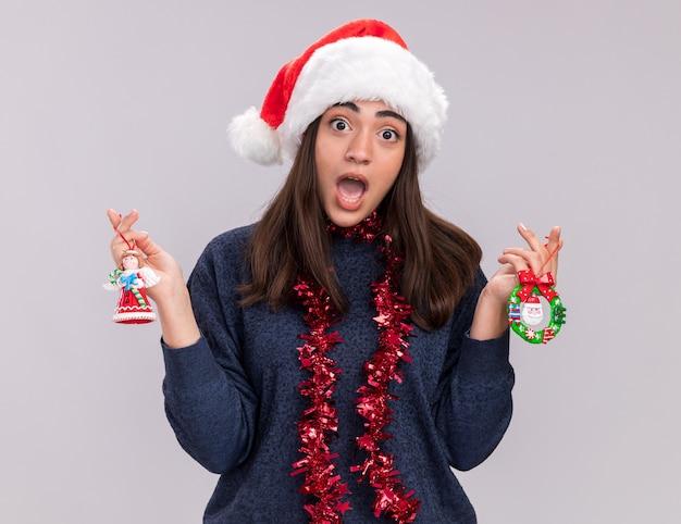 首の周りにサンタの帽子と花輪を持つ気になる若い白人の女の子は、クリスマスツリーのおもちゃを保持します 無料写真