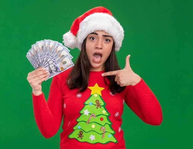 산타 모자와 불안 젊은 백인 여자 보유 및 복사 공간이 녹색 배경에 고립 된 돈에 포인트 무료 사진