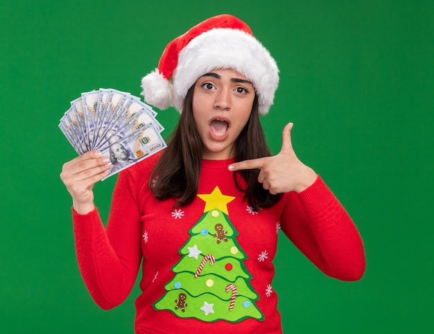 Anxious young caucasian girl with santa hat holds and points at money isolated on green background with copy space Free Photo