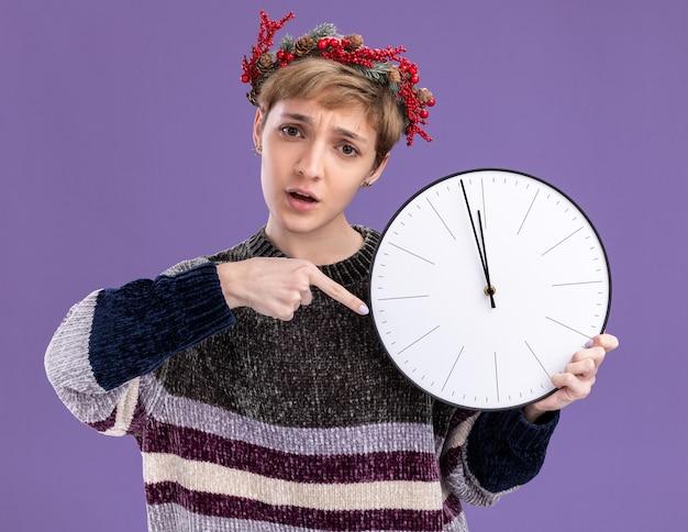 Ansioso giovane bella ragazza che indossa la corona di natale testa tenendo e indicando l'orologio isolato sulla parete viola Foto Gratuite
