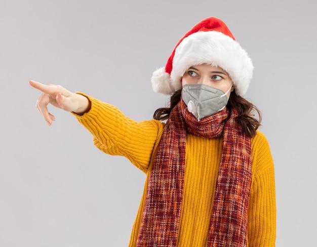 サンタの帽子と首の周りのスカーフと医療マスクを身に着けている不安な若いスラブの女の子は、コピースペースで白い背景で隔離された側を見て、指しています 無料写真