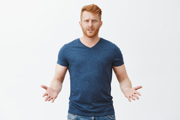 Any problem. portrait of confused questioned attractive masculine european redhead guy in blue t-shirt, gesturing with palms in clueless pose, waiting for explanation over gray wall Free Photo