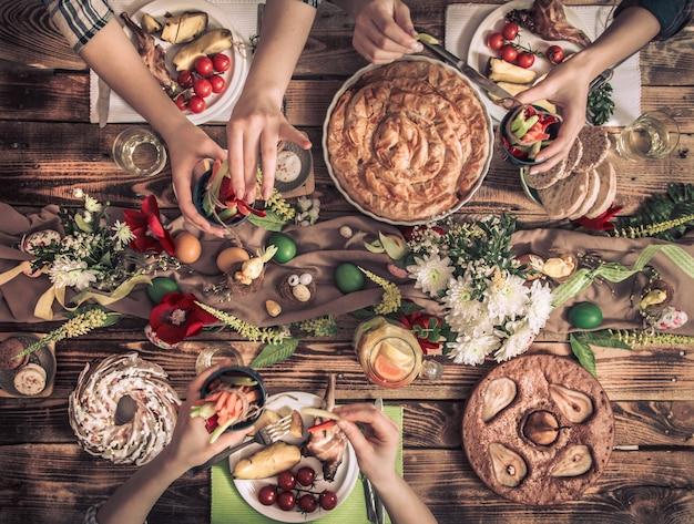 Квартира-праздник друзей или семьи за праздничным столом с мясом кролика, овощами, пирогами, яйцами, видом сверху. Premium Фотографии