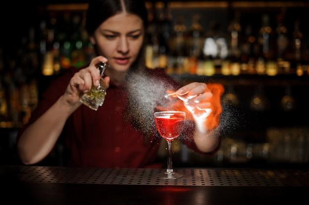 女性のバーテンダーがaperol注射器でカクテルグラスを振りかけ、ピートウイスキーカクテルとバーカウンターでスモーキーなメモを作る Premium写真