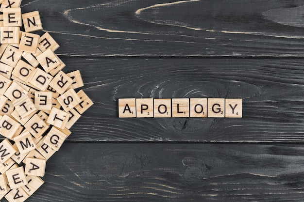 Apology word on wooden background Premium Photo