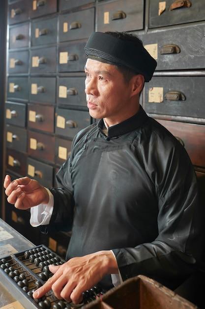 Аптекарь работник с помощью счеты Premium Фотографии
