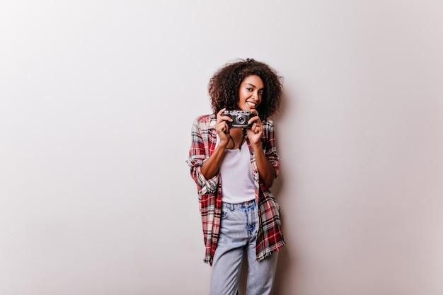 カメラが立っている魅力的な茶色の髪の女性。白で隔離の笑顔のアフリカの女性のショットグラファー。 無料写真