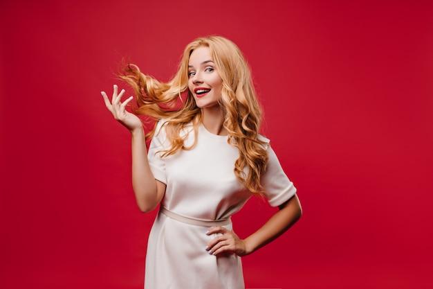 Привлекательная кавказская девушка играет с длинными волосами на красной стене. крытый фото привлекательной стильной женщины в платье. Бесплатные Фотографии