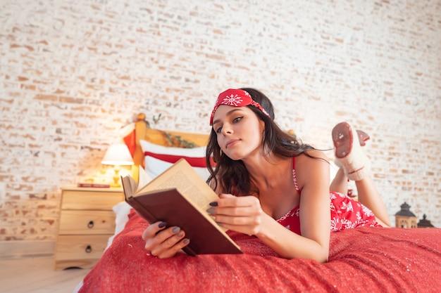 ベッドで休んで赤いパジャマで魅力的な長髪の女性 無料写真