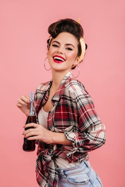 카메라에 미소 체크 무늬 셔츠에 매력적인 핀 업 여자. 병 분홍색 배경에 고립 된 매력적인 갈색 머리 여자의 스튜디오 샷. 무료 사진