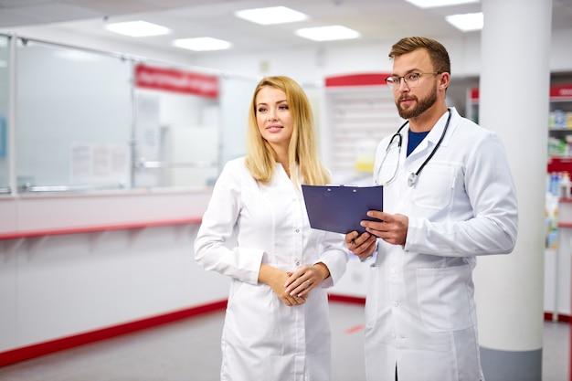 의사 소통하는 매력적인 두 백인 약사 프리미엄 사진