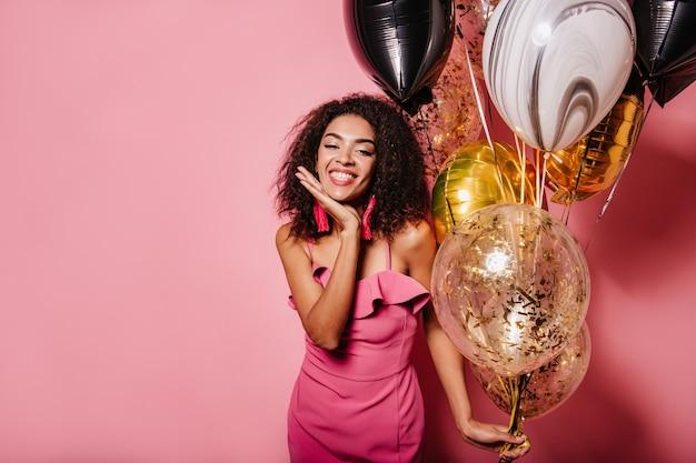 미소로 분홍색 벽에 포즈 매력적인 여자 무료 사진