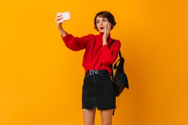 自撮り写真を撮るバックパックで魅力的な女性 無料写真