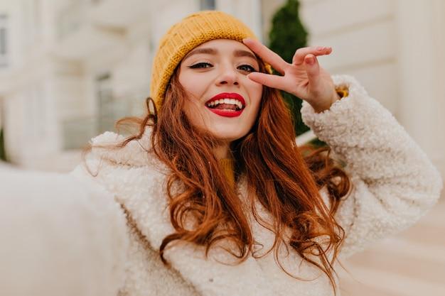 추운 겨울 날에 포즈 생강 머리를 가진 매력적인 여자. 아름 다운 Red-haired 여자의 야외 사진입니다. 무료 사진