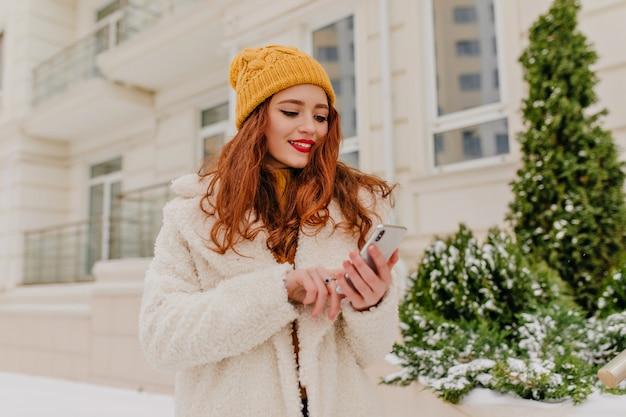 긴 헤어 스타일 문자 메시지와 함께 매력적인 여자. 행복 한 생강 여자의 겨울 초상화입니다. 무료 사진