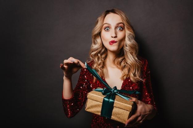 Привлекательная молодая женщина трогает ленту на новогоднем подарке Бесплатные Фотографии