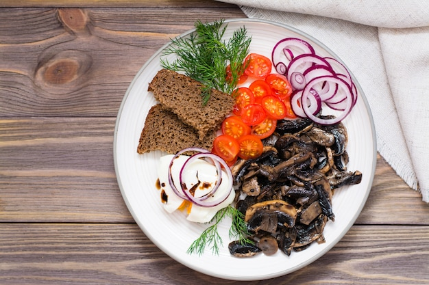 Appetizer of fried mushrooms, onions, tomatoes and poached eggs on a plate on a wooden table Premium Photo