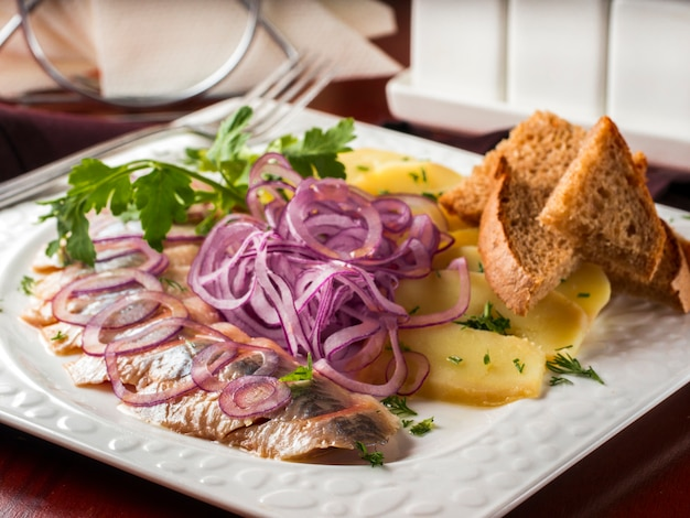 Appetizer of salted herring, red onion, potatoes and rye bread Premium Photo