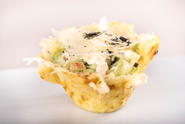 Appetizer with caeser salad and chicken fillet,  served in a parmesan basket,  white plate Premium Photo