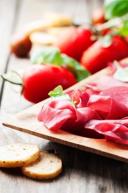 Закуска с итальянской брезаолой и помидорами Premium Фотографии