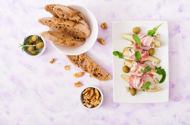 Закуска с грушей, голубым сыром, ветчиной прошутто и тостами для праздников на белой тарелке. Premium Фотографии