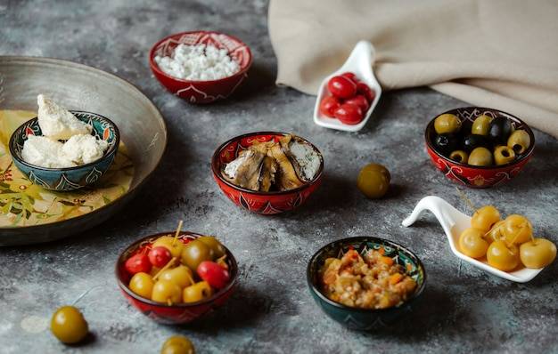 Appetizers in small sauce bowls containing marinated foods, olives and cream cheese Free Photo