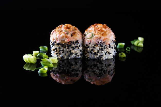 Appetizing baked sushi roll with fish, green onions on a black background with reflection menu and restaurant Premium Photo