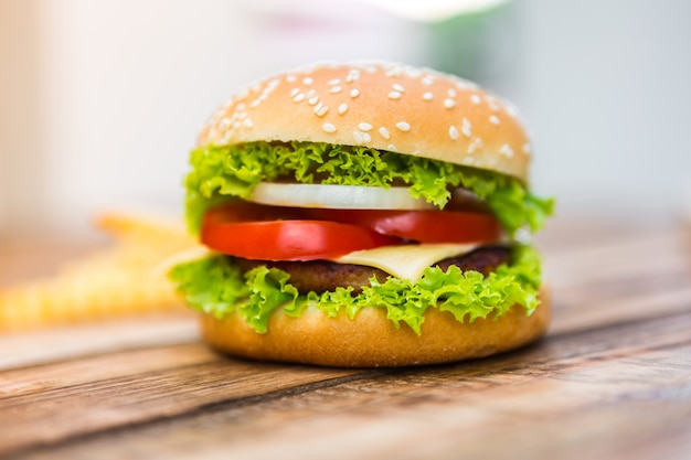 Appetizing cheeseburger on wooden table Free Photo