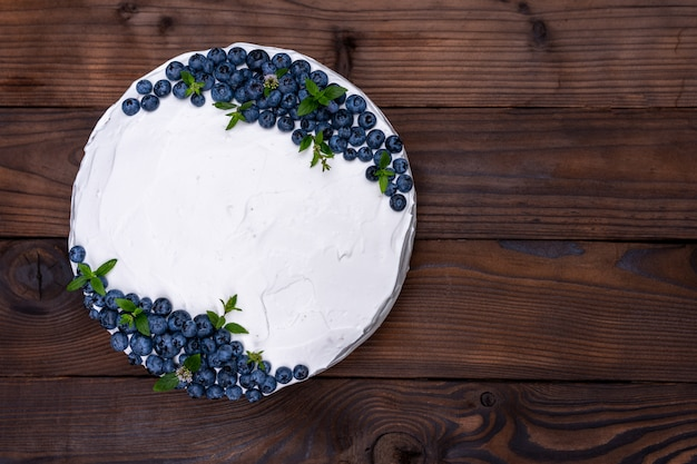 Appetizing cheesecake biscuit pillow decorated white cream blueberries and mint stands on wooden rustic table. sweet cake with piece on plate Premium Photo