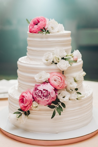 Appetizing fresh pastry cake covered by white cream icing and decorate sweet flower serving on table Premium Photo