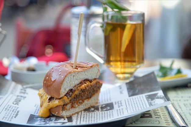 ストリートカフェで食欲をそそるハンバーガーとレモンとお茶のグラス Premium写真