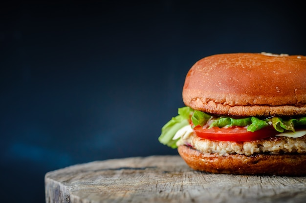Appetizing homemade burger on a wooden table on dark blue background Premium Photo
