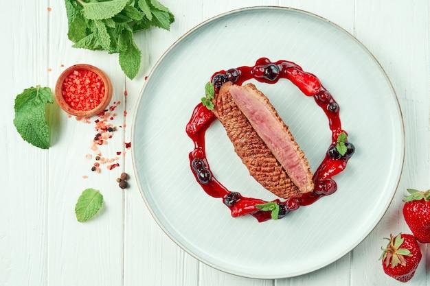 Аппетитная жареная утиная грудка с ягодным вареньем в тарелке на белом деревянном столе в составе с ингредиентами. обслуживание в ресторане Premium Фотографии