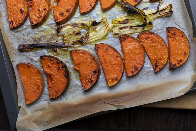 Appetizing roasted pumpkin slices on baking tray. with onion. Premium Photo