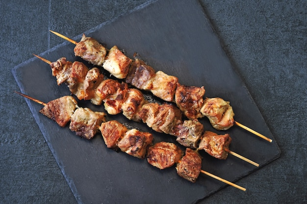 Appetizing ruddy kebabs on a dark stone surface. top view. Premium Photo