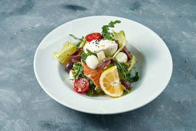 白い皿にトマト、サーモン、アンチョビ、クリームチーズの食欲をそそるサラダ。コンクリート表面 Premium写真