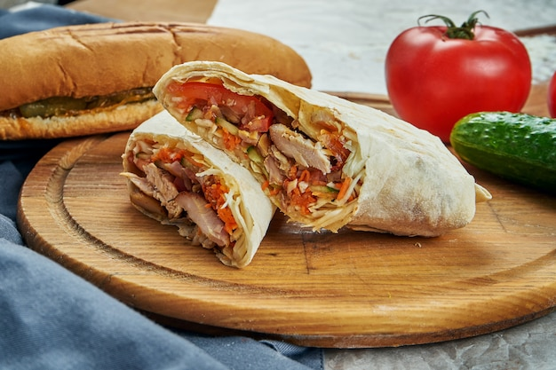 Appetizing shaurma or shawerma with meat, tomato, cabbage. chicken meat. kebab on wooden tray. close up, selective focus Premium Photo