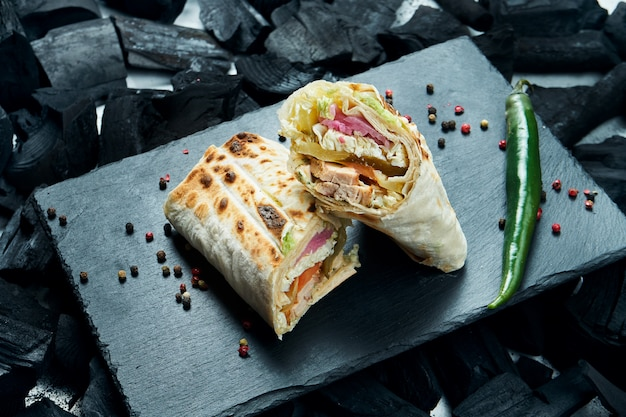 Appetizing shaurma or shawerma with spices and onions on a black slate tray on a surface of charcoal. kebab Premium Photo