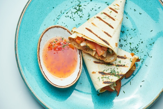 Аппетитный шаурма ролл с мясом, салатом и домашним соусом в тонком лаваше в синюю тарелку, изолированных в серой поверхности. восточная кухня нарезанный кебаб с жареным мясом. Premium Фотографии