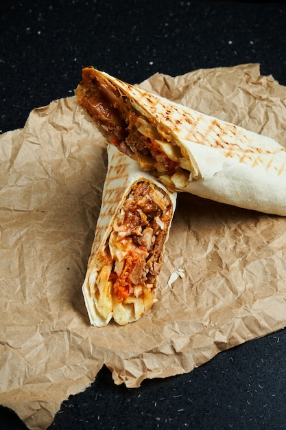 Аппетитный шаурма ролл с мясом, салатом и домашним соусом в тонком лаваше на крафт-бумаге на черной поверхности. восточная кухня нарезанный кебаб с жареным мясом. Premium Фотографии