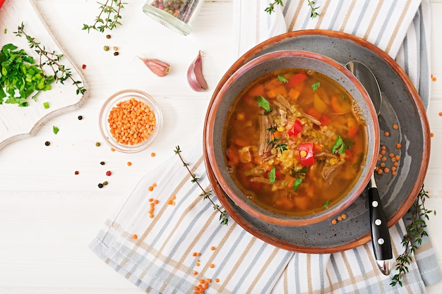 Appetizing soup with red lentils, meat, red paprika and fragrant thyme. Premium Photo