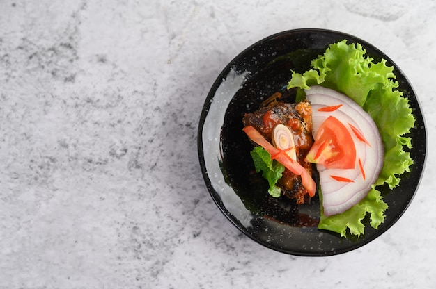 Appetizing spicy canned sardine salad in spicy sauce in black ceramic bowl Free Photo
